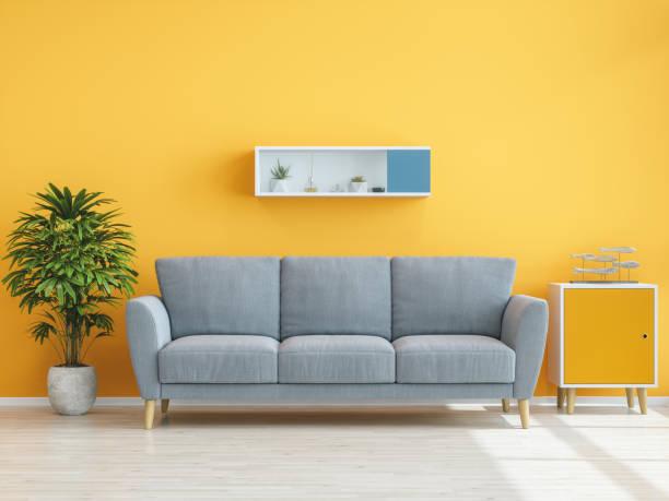 Sofa, Pflanze und Tisch mit gelber Wand – Foto