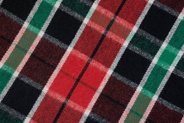 Soft and warm checkered wool blanket. Green and red plaid texture, macro shot. Wool plaid pattern. Textured surface of checkered cloth. stock photo