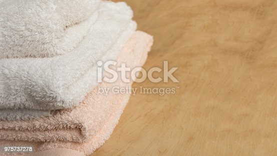 618327092istockphoto Soft bath towel on wooden background. 975737278