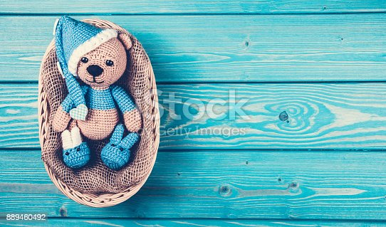 istock Soft bear cub lies in the basket. Knitted teddy bear in  hat.Copy space 889460492