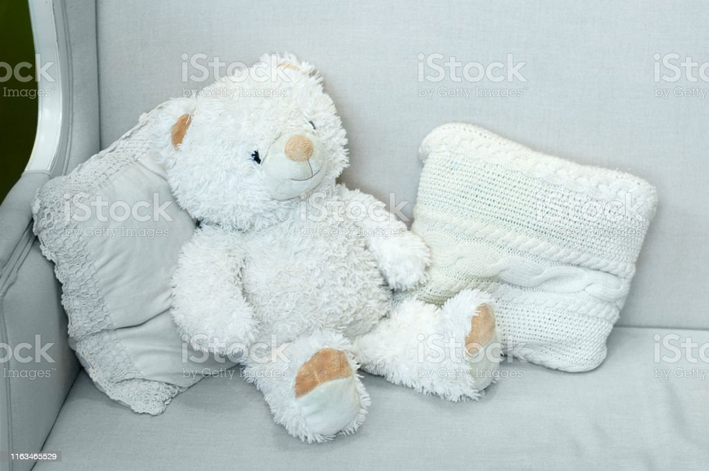 Soft big toy polar bear. On the couch with interior cushions.