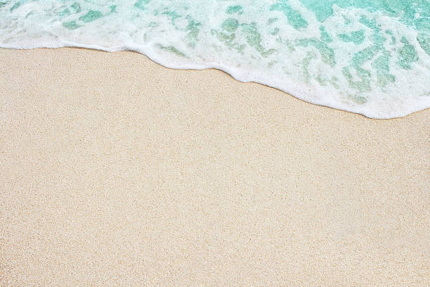 Soft blue ocean wave on sandy beach stock photo