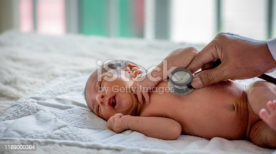 Soft blur of the doctor hands use stethoscope to check newborn baby health and take care him or cure the disease or disorder.