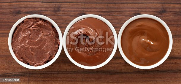 Three bowls containing soft chocolate stuff (mousse, spread and pudding)