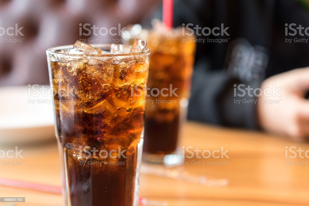 Soft drink on wooden table and men sitting