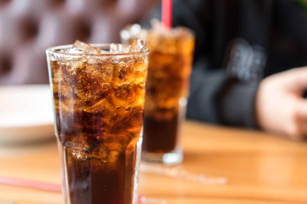alkoholfreies getränk am tisch aus holz und männer sitzen - alkoholfreies getränk stock-fotos und bilder