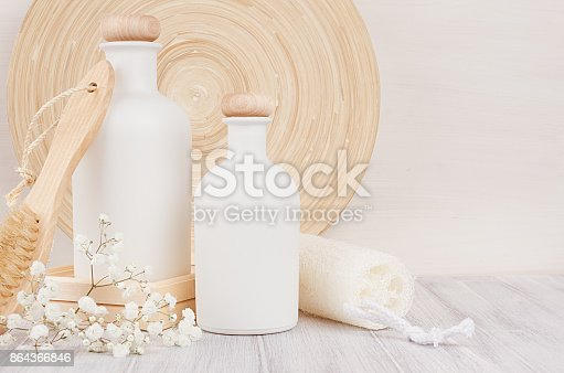 847096968 istock photo Soft elegant bathroom decor of white cosmetics bottles with comb, flowers on white wood board, mock up, copy space. 864366846
