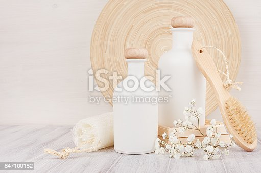 847096968 istock photo Soft elegant bathroom decor, template of white cosmetics bottles with comb, flowers on white wood board,copy space. 847100182