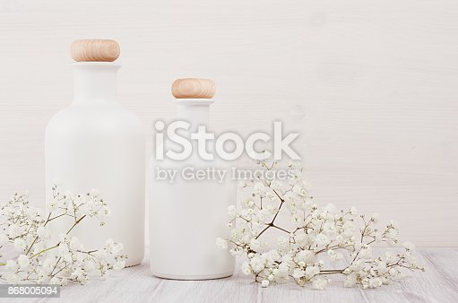 istock Soft elegant home decor with white bottles and small flowers on white wooden plank. 868005094
