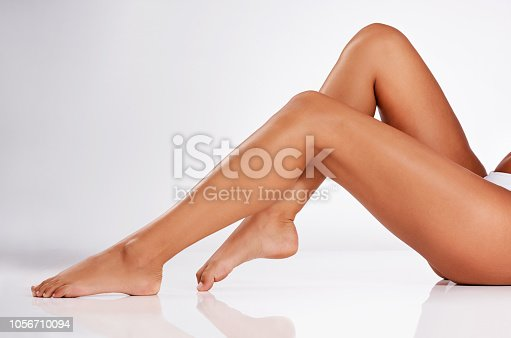 Studio shot of an unrecognizable young woman's legs against a gray background