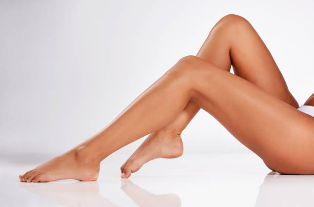 Soft, flawless skin Studio shot of an unrecognizable young woman's legs against a gray background leg stock pictures, royalty-free photos & images