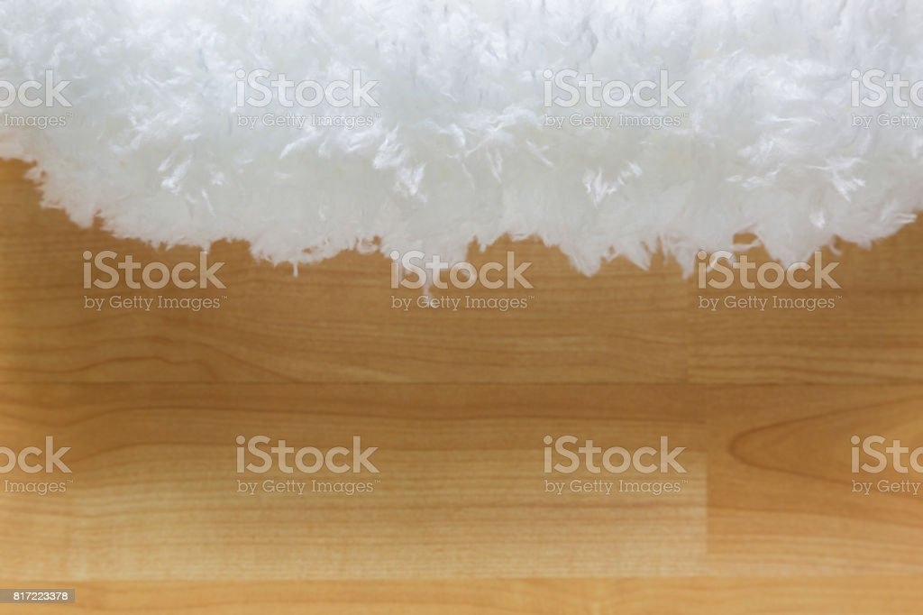 Soft fluffy white cloud like fur microfiber fabric on blurred wooden background stock photo