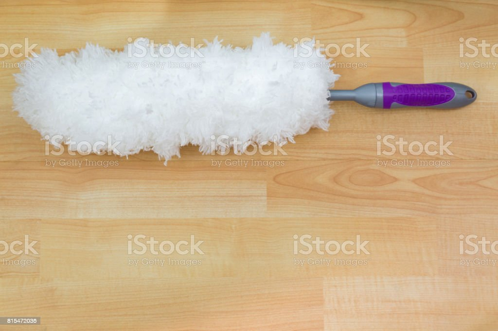 Soft fluffy white furry feather static duster with purple handle on wooden background stock photo