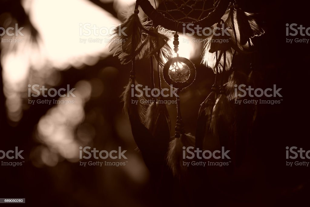 Soft focus Dream Catcher with a flare from the sun set on the background bokeh nature. Native american dream catcher. (sepia tone) boho chic, ethnic amulet. stock photo