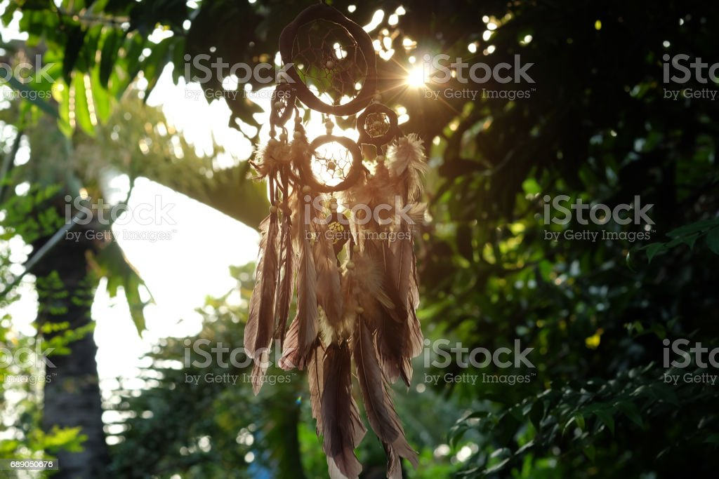 Soft focus Dream Catcher with a flare from the sun set on the background bokeh nature. Native american dream catcher. (Vintage style) boho chic, ethnic amulet. stock photo