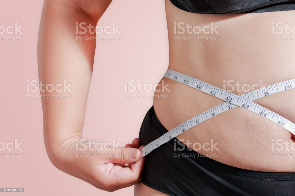 soft focus measure your body fat percentage with measuring tape for fat or obesity background stock photo
