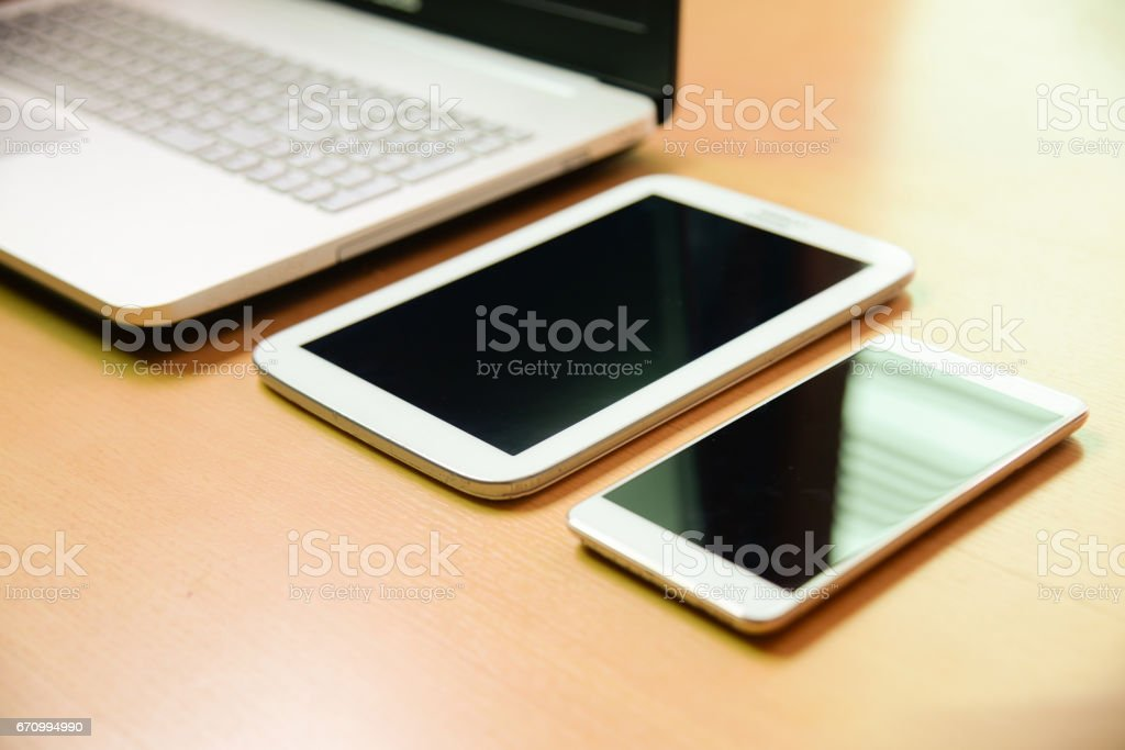 Soft focus notebook computer with taptet and smarth phone on wooden desk background stock photo