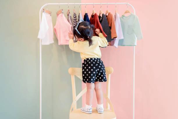 soft focus z dwóch lat dziecko wybór własnych sukienek z dziecięcych cloth rack - odzież zdjęcia i obrazy z banku zdjęć