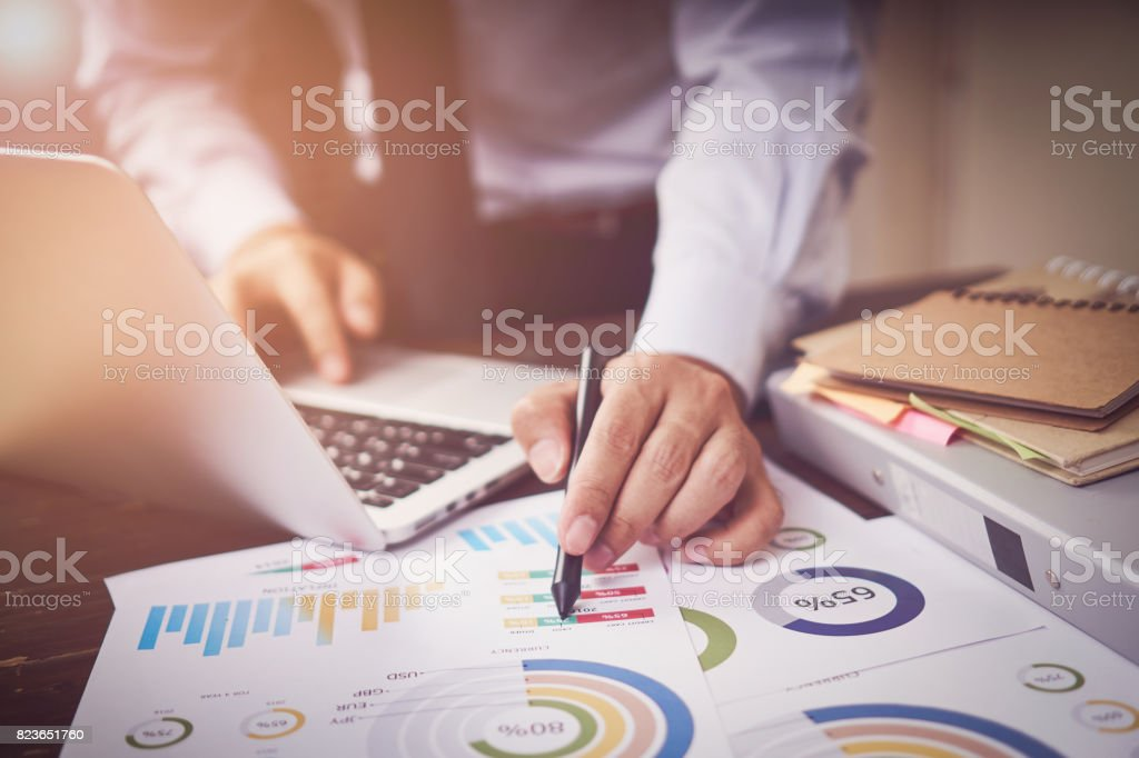 soft focus of businessman hand working laptop on wooden desk in office in morning light. The concept of modern work with advanced technology. vintage effect stock photo