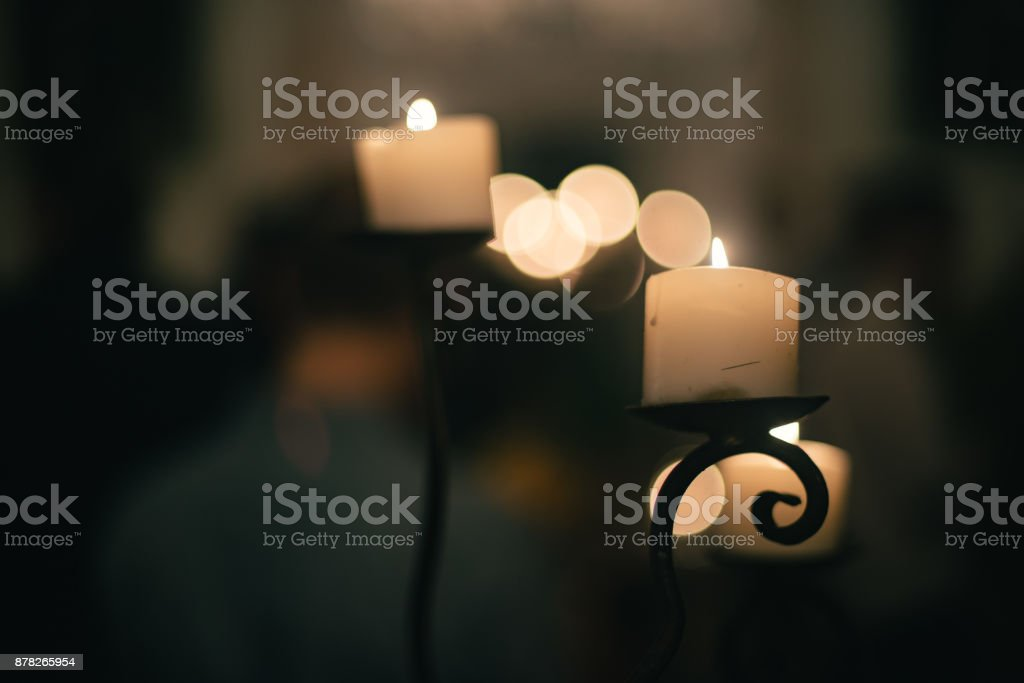 Soft focus of candle and candlestand with bokeh and minimal grain stock photo