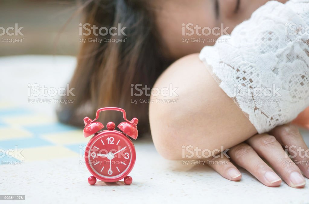 Soft focus of closeup red alarm clock with blurred sleeping woman on marble desk background , relaxation of asian woman concept stock photo