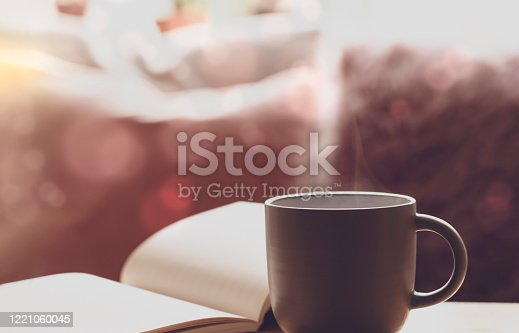 Soft focus of mug of aroma tea  with open book and blurred cusion background with bright light in the morning, Cozy sence of afternoon tea with notebookin pastel tone