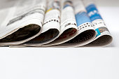istock soft focus of newspapers folded and stacked in pile. Concept of print media, news and publishing industry 1266780408