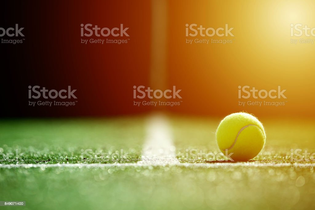 soft focus of tennis ball on tennis grass court with sunlight stock photo
