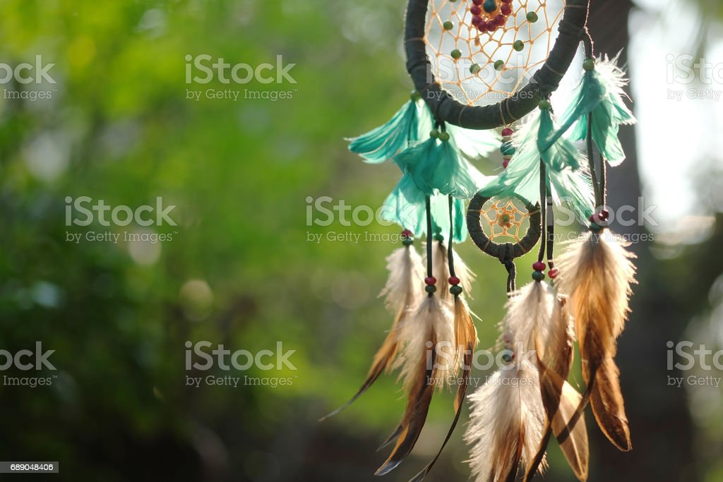 Soft focus on Dream Catcher Blue Coral with natural background in vintage style. Sunset light percussion dream catcher. boho chic, ethnic amulet. stock photo