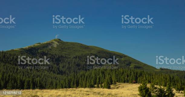 Photo of soft focus on foreground trees Carpathian mountains panoramic landscape highland forest ridge scenic view spring time with moon shape near top