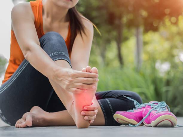 mulher de foco suave massageando o pé dela doloroso durante o exercício.   executando o conceito de ferimento do esporte. - pé humano - fotografias e filmes do acervo
