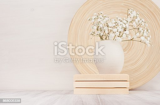 istock Soft home decor of beige bamboo dish and white small flowers in ceramic vase  on white wood background. Interior. 868005338