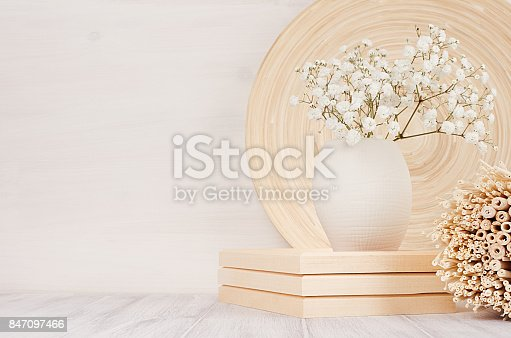 istock Soft home decor of beige bamboo dish, twigs and white small flowers in ceramic vase  on white wood background. Interior. 847097466
