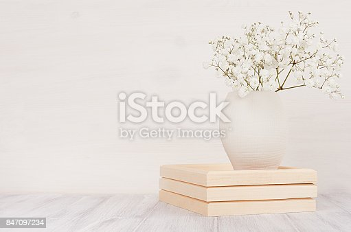 istock Soft home decor of white small flowers in ceramic vase on white wood background. Interior.