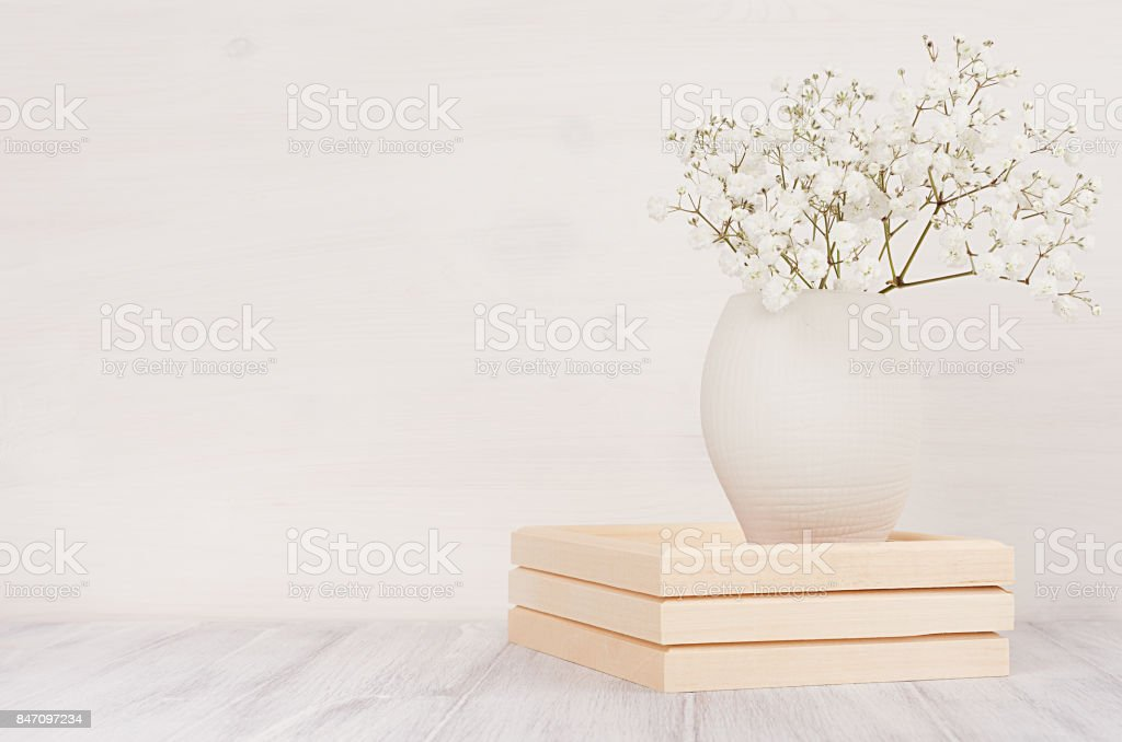 Soft home decor of white small flowers in ceramic vase on white wood background. Interior.'n stock photo