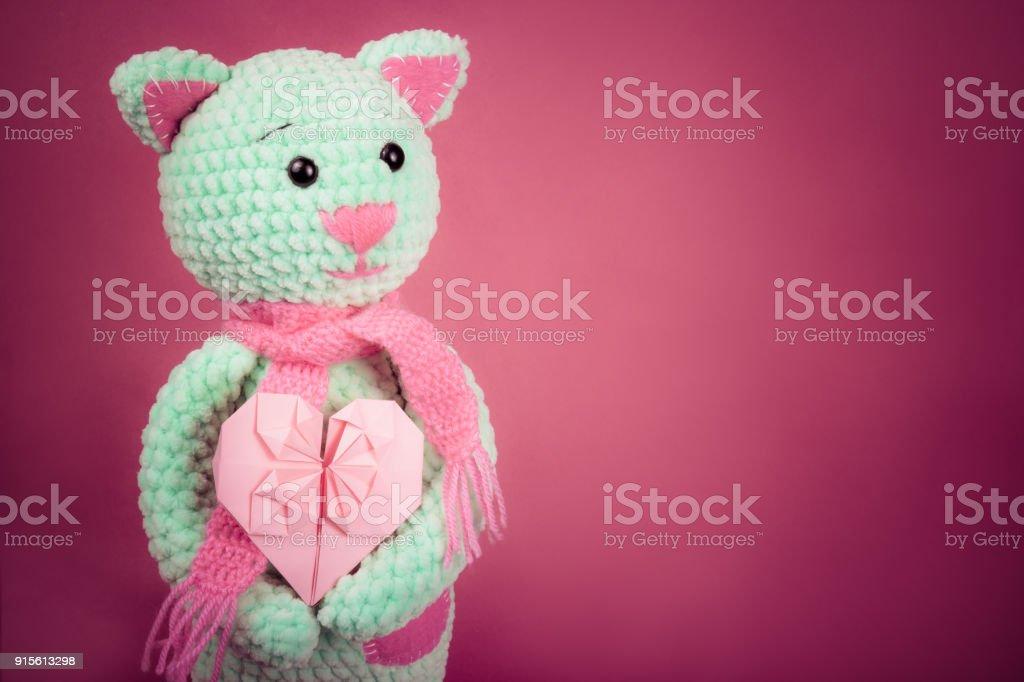 Suave punto cat San Valentín tarjeta y sobre fondo rosa. Juguete suave del tejido. Regalo romántico. Copia espacio - foto de stock