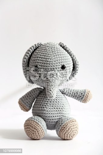 Soft knitted toy and on white background.