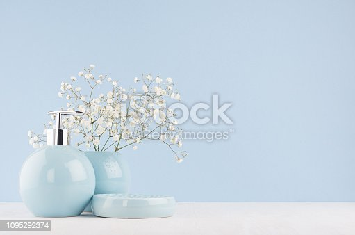 istock Soft light fresh bathroom interior in pastel blue color with white bouquet and smooth ceramic bowls on wood table. 1095292374