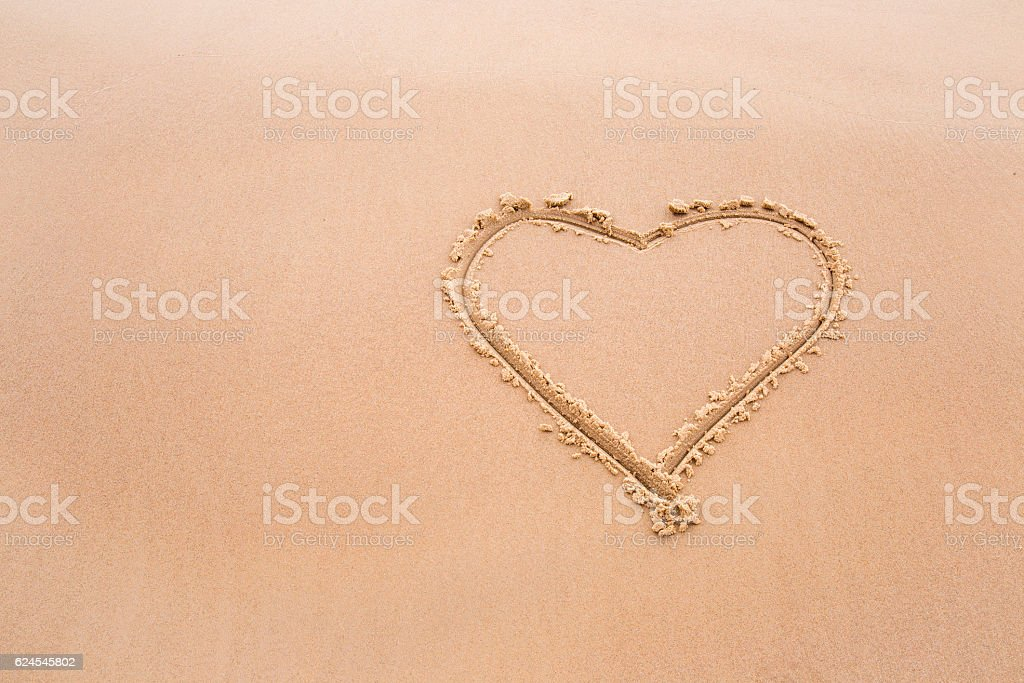 Soft love heart drawn on wet sand by the waves. stock photo