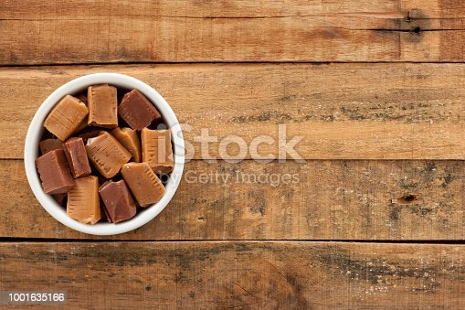 Top view of white bowl full of soft milk candy over wooden table