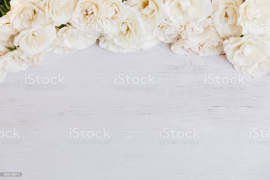 Soft off white roses framing wooden background stock photo