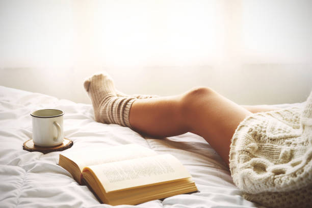 Soft photo of woman on the bed with old book and cup of coffee stock photo