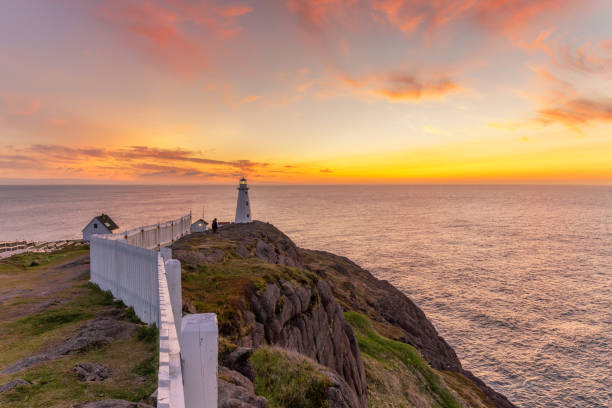 Soft pink and orange clouds light up the sky before sunrise over a white lighthouse sitting at the edge of a rocky cliff.