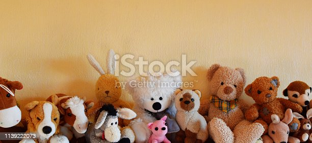 Soft plush toys for children sitting in row, different toy animals for kids on yellow wall background with copy space as horizontal banner.