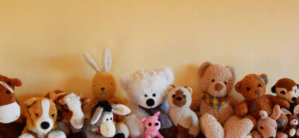 Soft plush toys for children sitting in row Soft plush toys for children sitting in row, different toy animals for kids on yellow wall background with copy space as horizontal banner. fluffy stock pictures, royalty-free photos & images