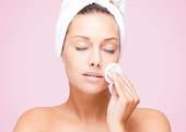 """""""A beautiful woman is applying a lotion, like anti-aging or moisturizer in her face.She has a towel around her head and uses a cotton against her skin."""""""