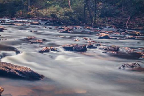 617378218 istock photo soft slow moving creek below a dam 451665599