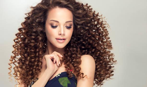 kusursuz genç kızın yüzünde yumuşak gülümseme. hacimli, parlak ve kıvırcık saç modeli ile kahverengi saçlı kadın. - kabarık saç stok fotoğraflar ve resimler