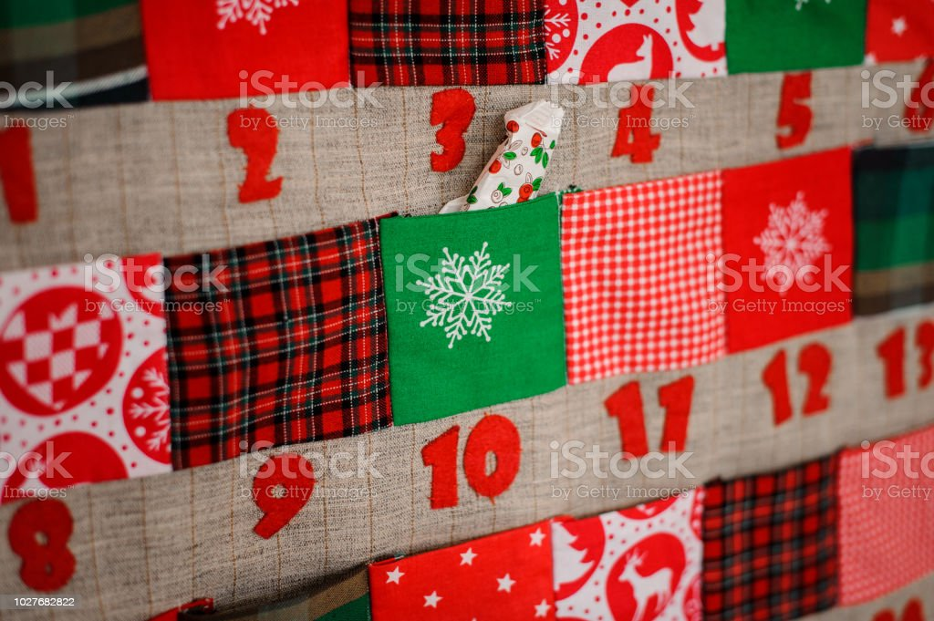 Soft textile Christmas calendar with pockets on the wall stock photo