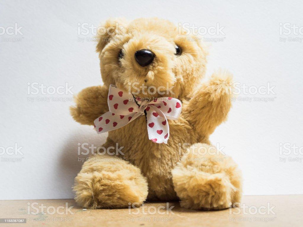 Soft toy fluffy bear sitting on wooden board